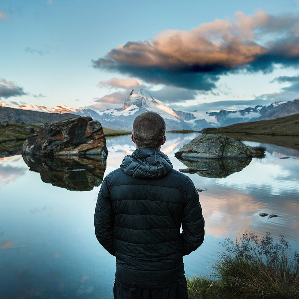 Man from Back Looking at a Lake in the Montains